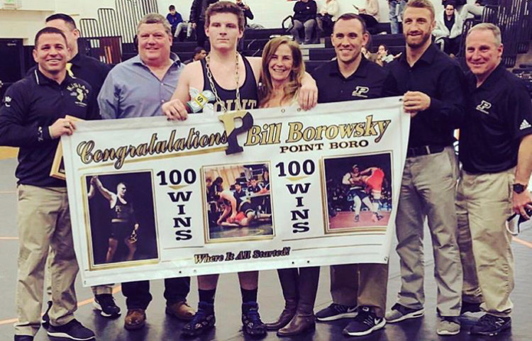 Billy+holding+his+100th+win+banner+with+his+family+and+coaches.