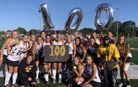 Senior Jordan Carr (center) after scoring her 100th career goal.