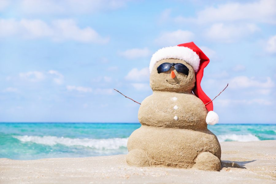 Smiling+sandy+snowman+in+red+santa+hat+on+the+sea+beach.+Holiday+concept+can+be+used+for+New+Year+and+Christmas+Cards